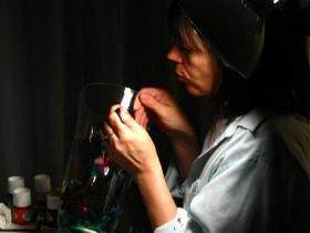 A picture of artist Alison Carol Blackburn painting a crystal vase